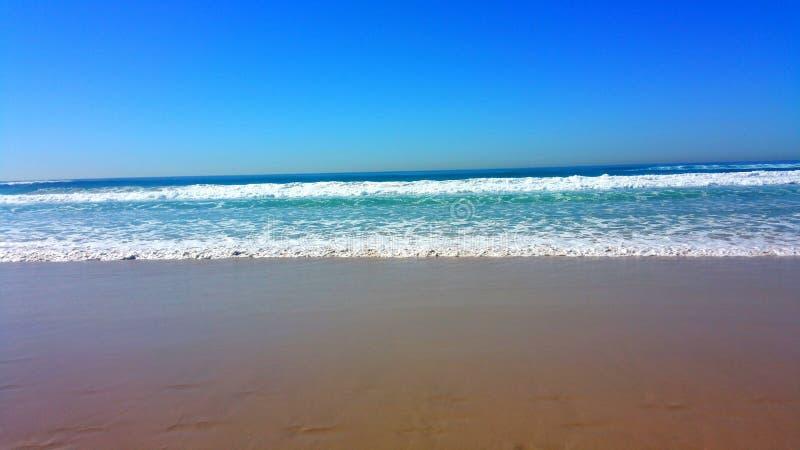 La beauté des couleurs de l'eau, du sable et du pied fait un pas enlevant photographie stock