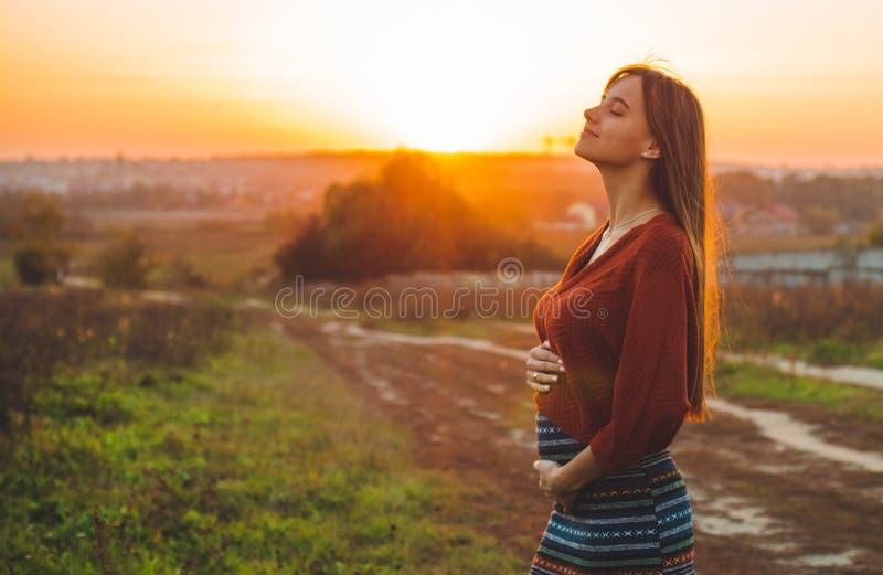 La beauté romantique est extérieur enceinte de fille appréciant la nature tenant son beau modèle d'automne de ventre en nature da images libres de droits