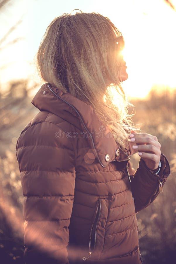 La beauté a tiré d'une femme dans le domaine au coucher du soleil image libre de droits
