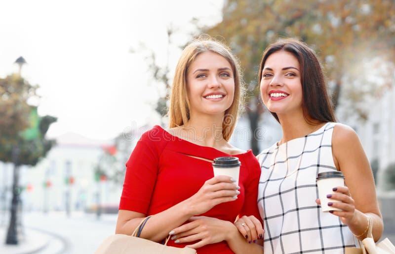 La bebida atractiva de las mujeres jovenes se lleva el café en ciudad del verano imágenes de archivo libres de regalías