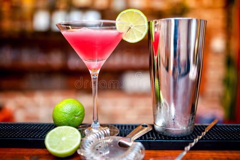 La bebida cosmopolita del cóctel en el casino y la barra sirvió con la cal fotografía de archivo