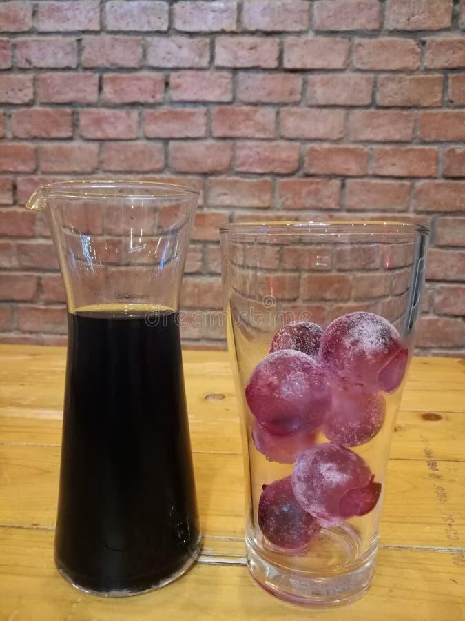 La bebida del verano, las uvas frescas refresco y el cubo de la bola de las uvas del hielo en vidrio del tarro con el ladrillo de foto de archivo