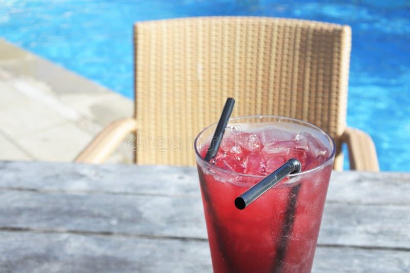 La bebida roja del cóctel con hielo sirvió en una tabla del poolside en un trop fotografía de archivo