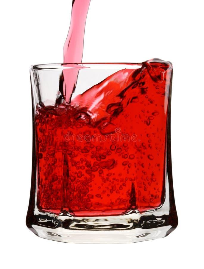 La bebida roja se está vertiendo en el vidrio