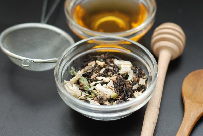 La bebida sana del té herbario de Acaccia en cuenco y el tamiz sobre fondo negro copian el espacio Bebida sana, frialdad imagen de archivo