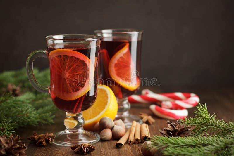 La bebida tradicional de la Navidad reflexionó sobre el vino con la fruta cítrica y las especias en fondo de madera rústico fotografía de archivo libre de regalías