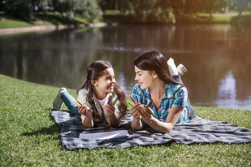 La bei madre e daighter stanno trovando insieme sulla coperta e stanno esaminandose Stanno sorridendo Le ragazze sono fotografia stock libera da diritti