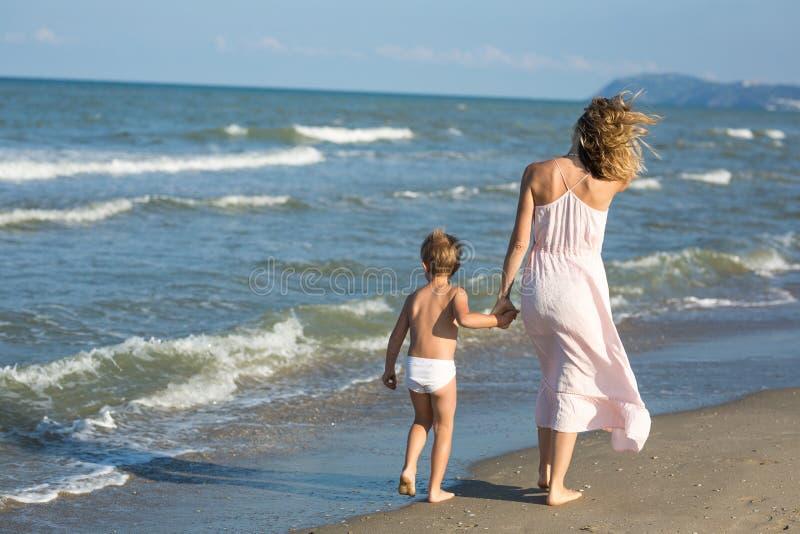 La bei mamma e bambino felici camminano lontano lungo la spiaggia del mare, salto del vento immagini stock