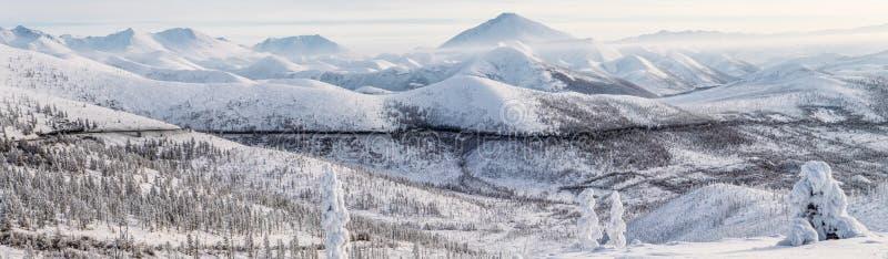 la bei strada ed alberi innevati dell'inverno in neve hanno ricoperto le montagne, strada principale di kolyma, fotografia stock