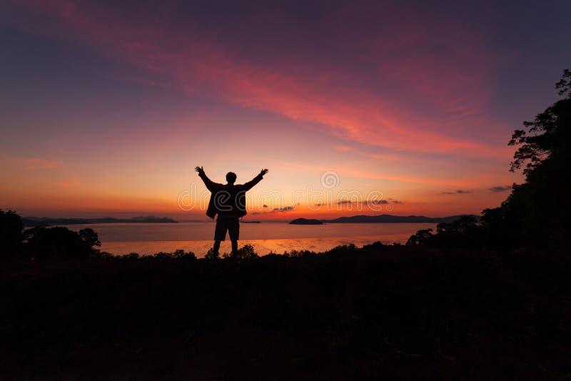 La bella alba drammatica con la condizione dell'uomo alzata-su arma il enjo fotografia stock