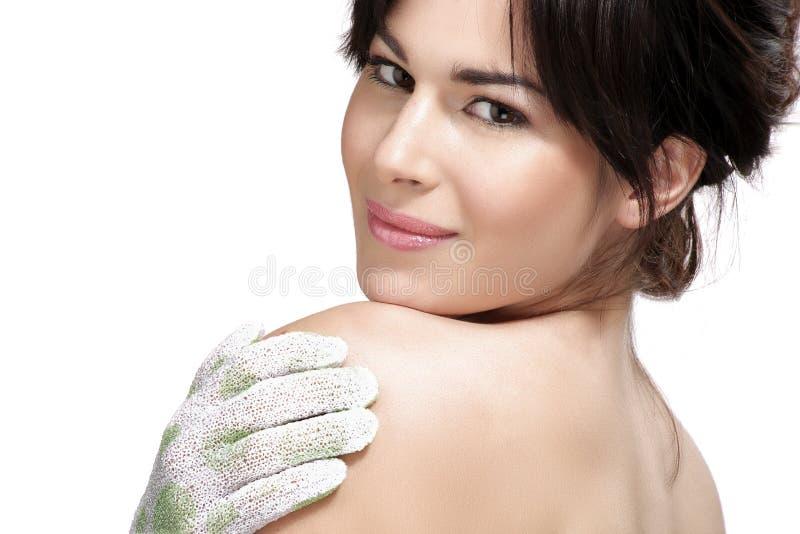 La bella applicazione della giovane donna sfrega il guanto sulla sua pelle perfetta immagine stock libera da diritti