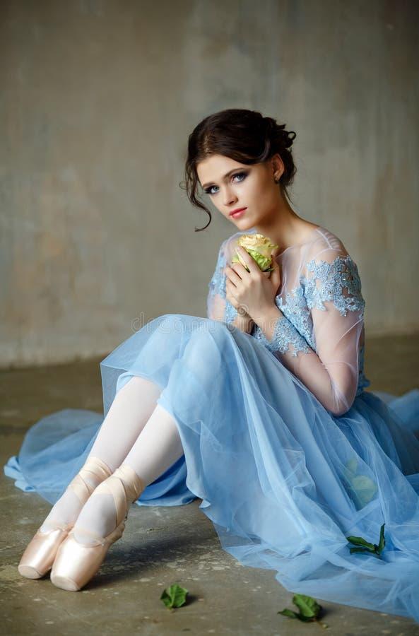 La bella ballerina graziosa della ragazza in un vestito blu e il pointe si siedono fotografia stock