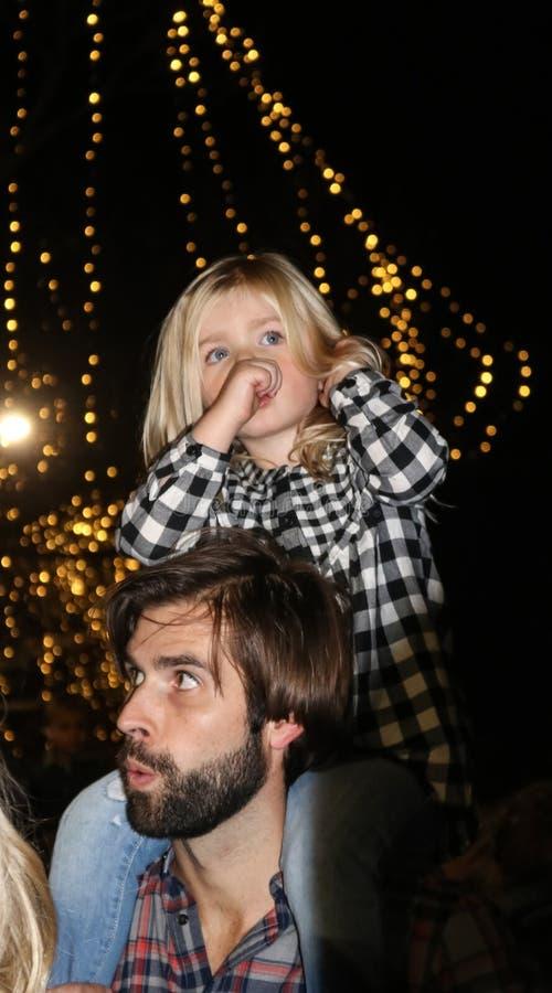 La bella bambina bionda con il suo pollice nella sua bocca e una guida della camicia di plaid sui suoi padri mette con le luci di immagine stock