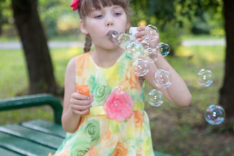 La bella bambina a colori il vestito soffia le bolle immagine stock libera da diritti