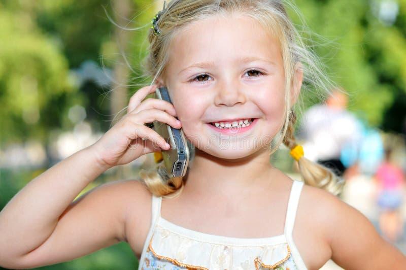 La bella bambina comunica da un telefono mobile fotografia stock libera da diritti