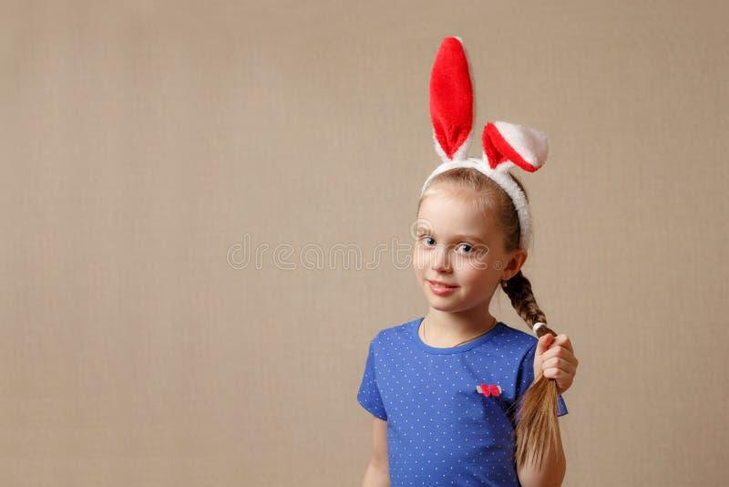 La bella bambina con le orecchie di coniglio tiene i suoi capelli fotografia stock