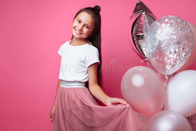 La bella bambina, con le palle su fondo rosa, celebra il compleanno fotografia stock