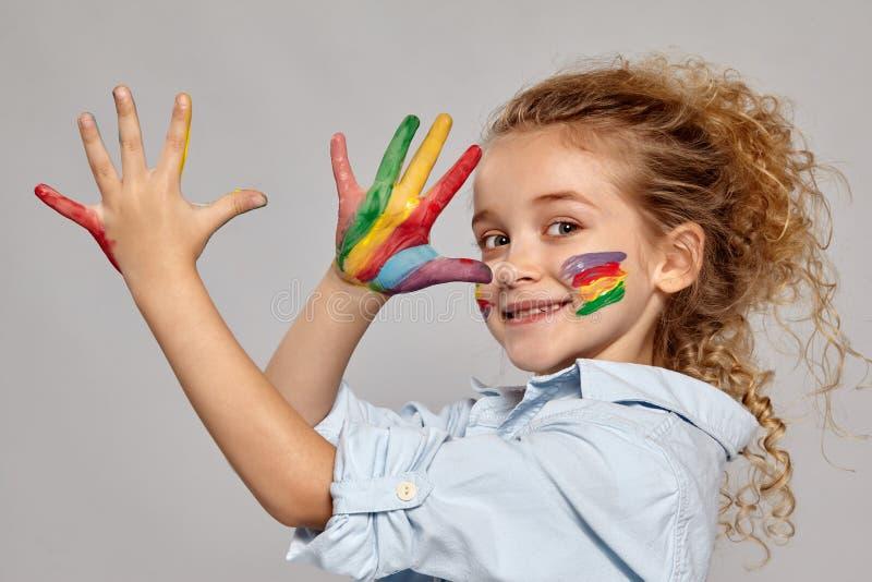 La bella bambina con mani e guance dipinte sta posando su un fondo grigio fotografia stock