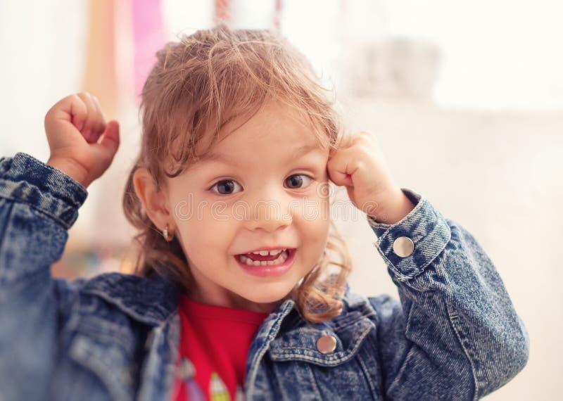 La bella bambina emozionante si tiene per mano su. fotografia stock libera da diritti
