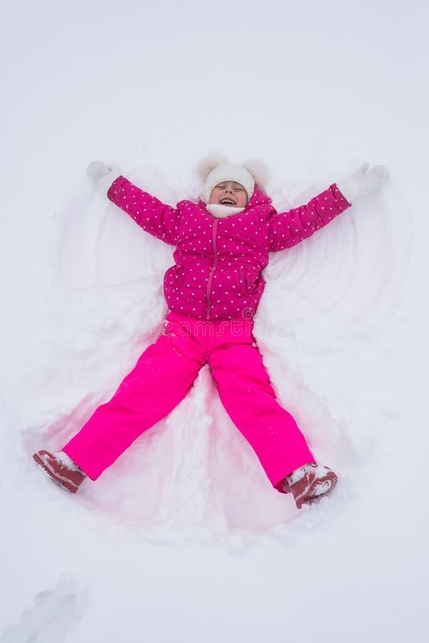 La bella bambina fa un angelo in un parco, vista superiore della neve immagini stock