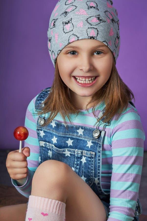 La bella bambina mangia la caramella ritratto di modo di un bambino della ragazza grande fotografia stock libera da diritti