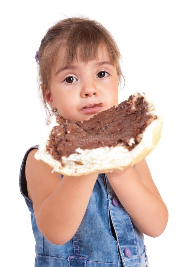 La bella bambina mangia il pane con il Cr del cioccolato immagine stock libera da diritti