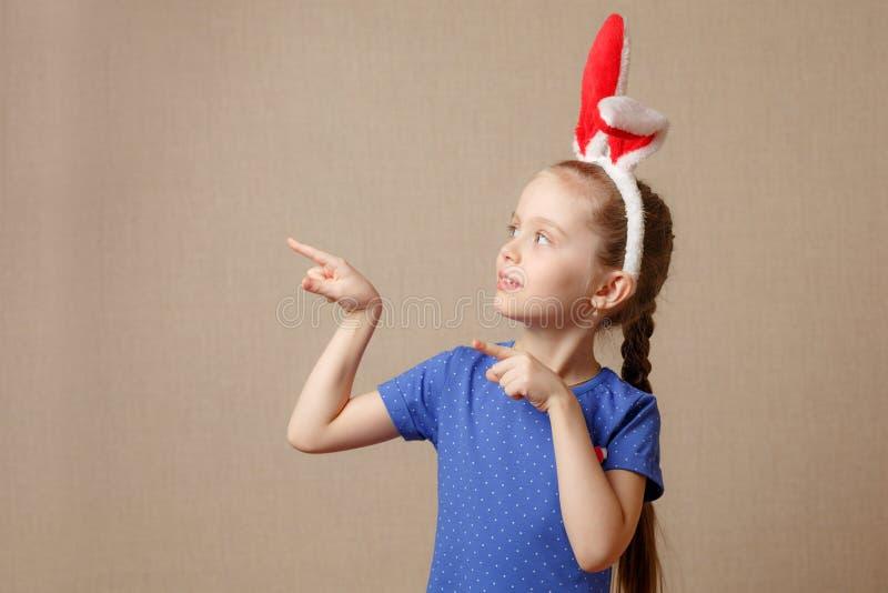 La bella bambina si è vestita in orecchie del coniglietto di pasqua su un fondo d'annata fotografia stock libera da diritti