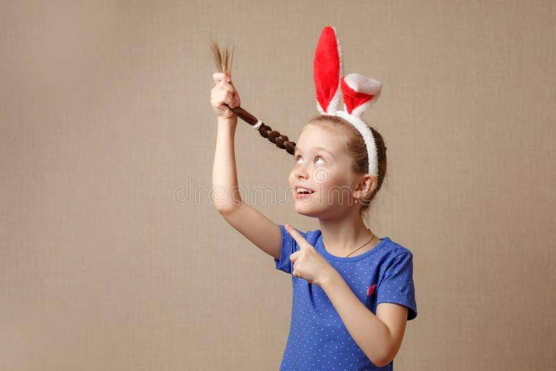 La bella bambina si è vestita in orecchie del coniglietto di pasqua su un fondo d'annata immagini stock libere da diritti