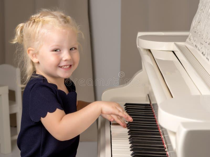 La bella bambina sta giocando su un pianoforte a coda bianco fotografie stock libere da diritti