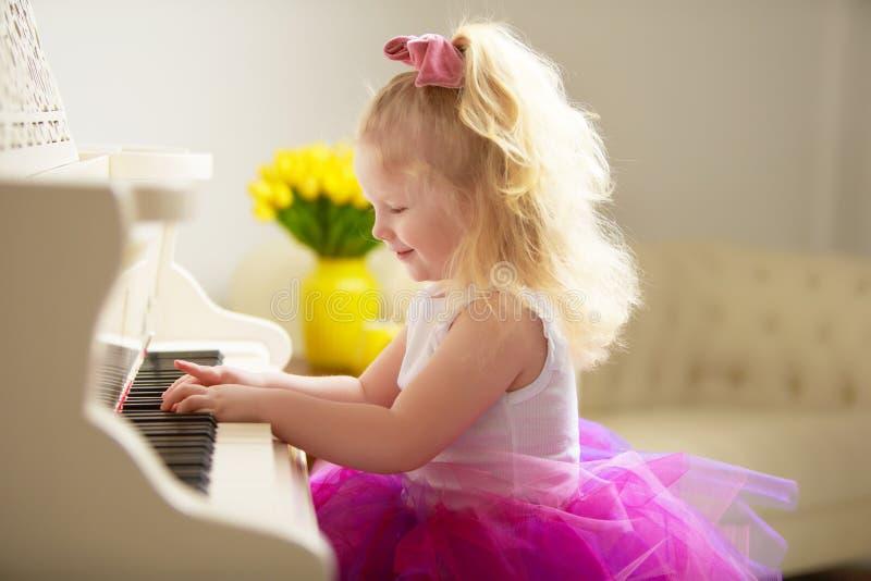 La bella bambina sta giocando su un pianoforte a coda bianco fotografia stock libera da diritti