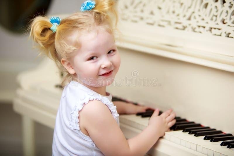 La bella bambina sta giocando su un pianoforte a coda bianco immagine stock libera da diritti