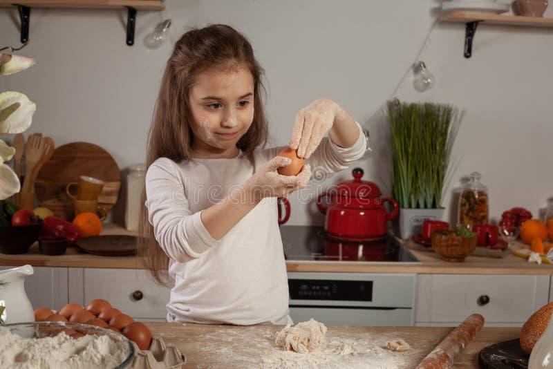 La bella bambina vestita in una blusa bianca sta producendo una pasta per cuocere un pane ad una cucina immagine stock