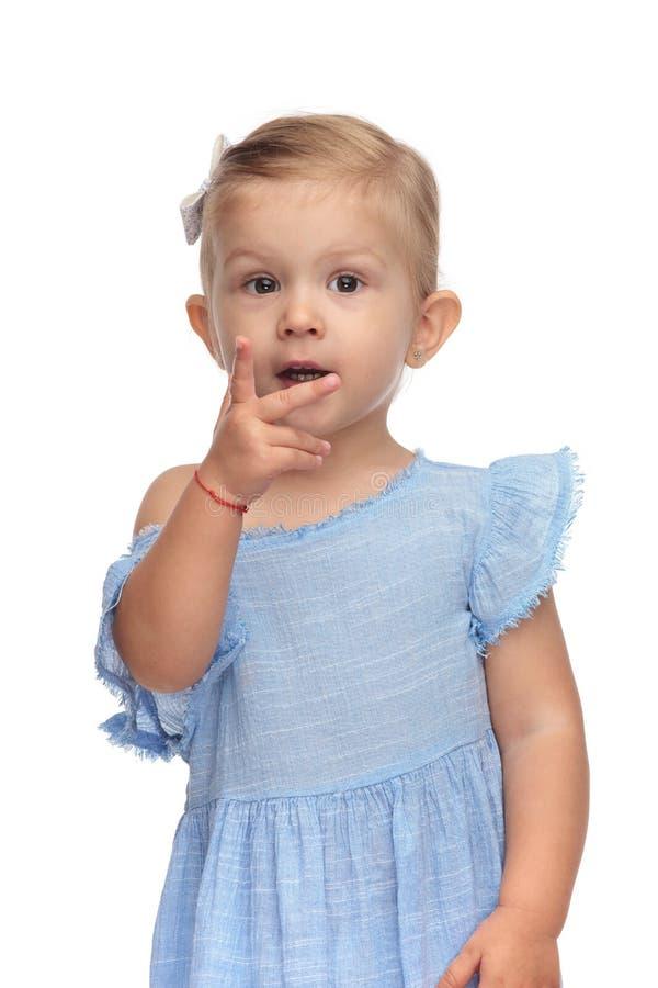 La bella bambina vi indica che può contare immagini stock