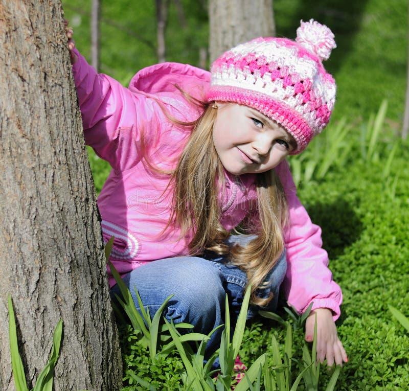 La bella bambina vicino ad un albero di fioritura fotografia stock