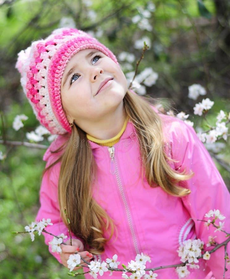 La bella bambina vicino ad un albero di fioritura fotografie stock