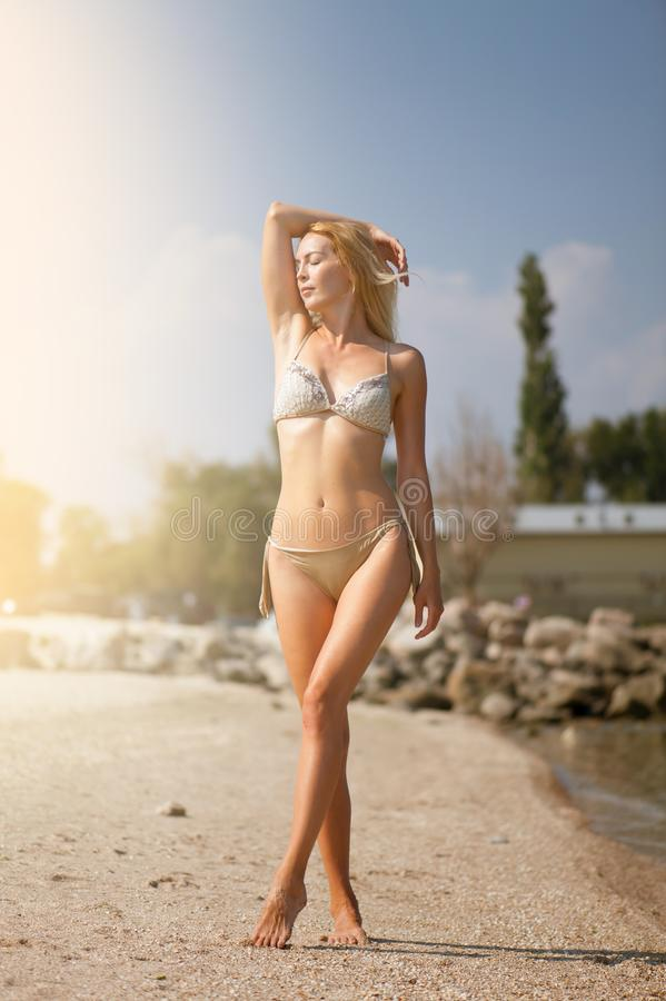La bella bionda esile della ragazza in un bikini alla moda beige prende il sole sulla spiaggia nella località di soggiorno fotografie stock