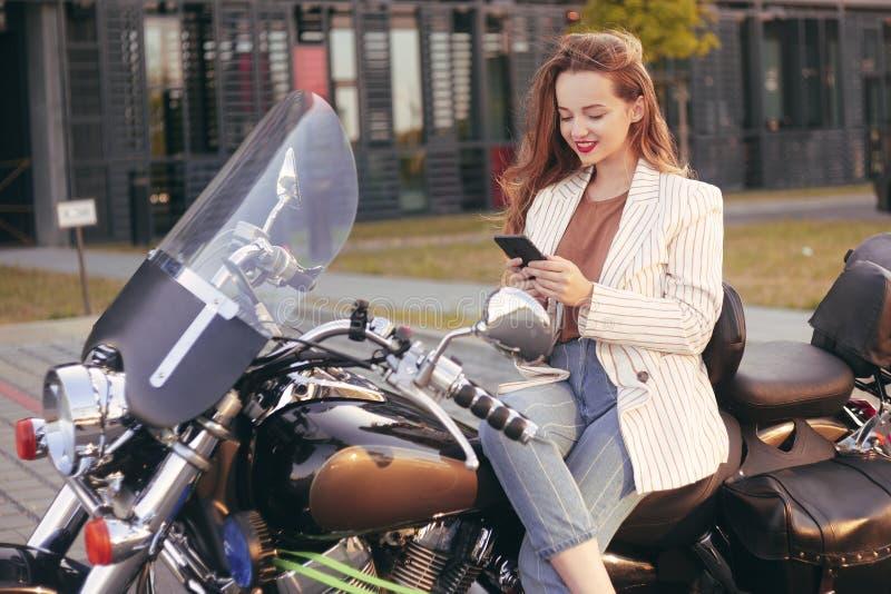 La bella bionda si siede su un motociclo vicino all'ufficio La ragazza è venuto a lavorare ad un motociclo La ragazza sta parland fotografie stock
