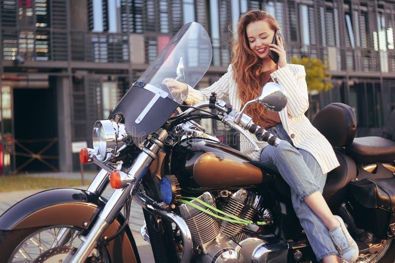 La bella bionda si siede su un motociclo vicino all'ufficio La ragazza è venuto a lavorare ad un motociclo La ragazza sta parland fotografia stock libera da diritti