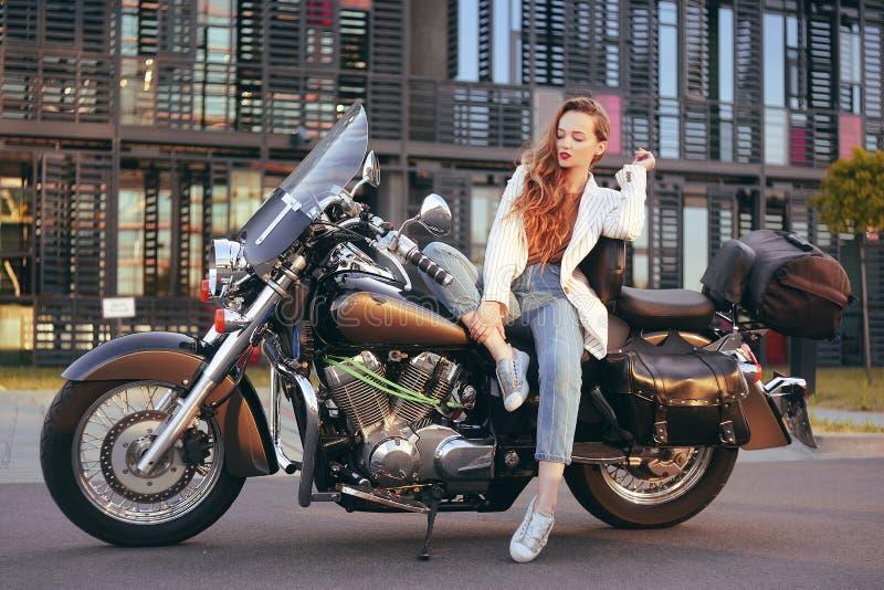 La bella bionda si siede su un motociclo vicino all'ufficio La ragazza è venuto a lavorare ad un motociclo Successo La ragazza si immagine stock libera da diritti
