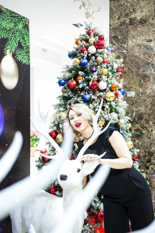 La bella bionda in un vestito nero abbraccia la figura di un cervo vicino all'albero di Natale immagini stock