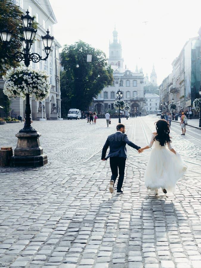 La bella coppia allegra della persona appena sposata sta tenendosi per mano mentre correva lungo la via soleggiata della città Vi fotografie stock