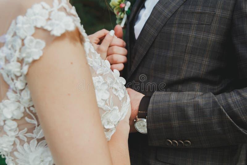 La bella coppia di nozze nella foresta la sposa con il velo di Tulle ed il vestito elegante lombo-sacrale aperto sta toccando lo  fotografie stock