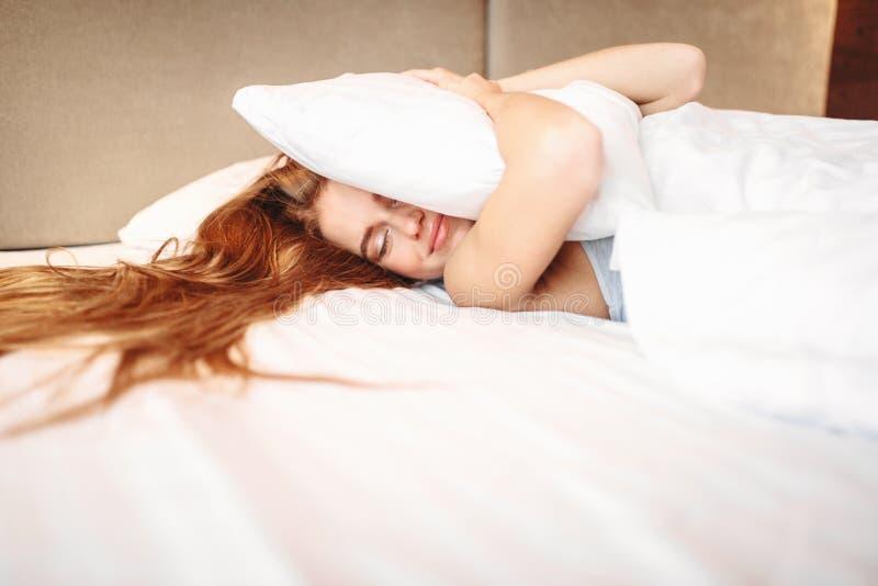 La bella donna abbraccia il cuscino, svegliante immagini stock