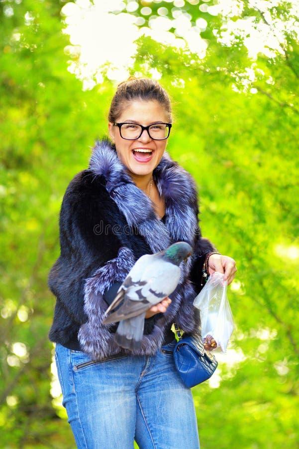 La bella donna alimenta i piccioni nel parco di autunno e ride immagini stock
