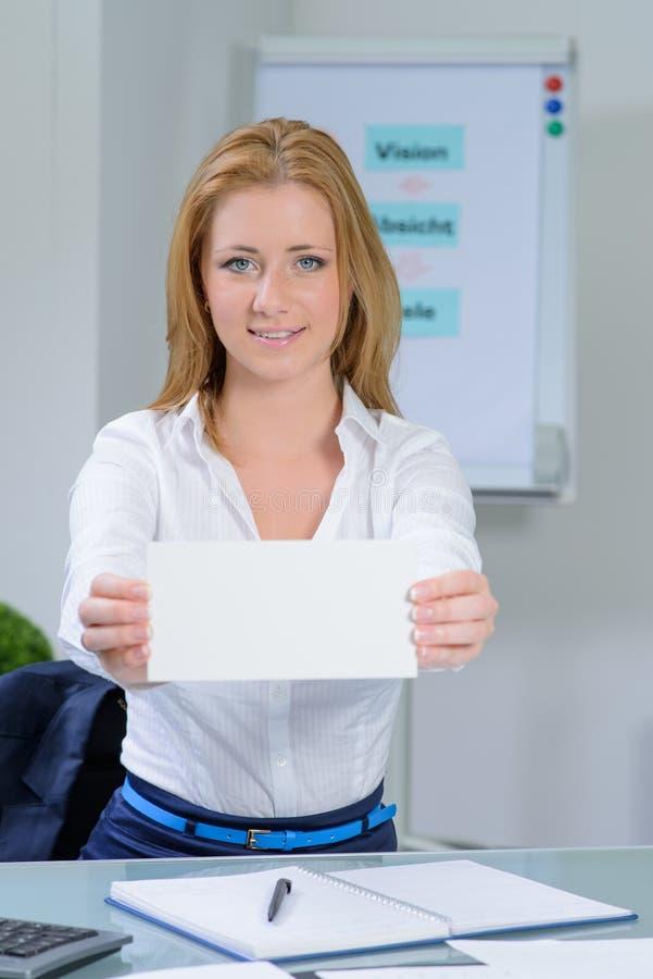 La bella donna all'ufficio mostra il biglietto da visita immagini stock