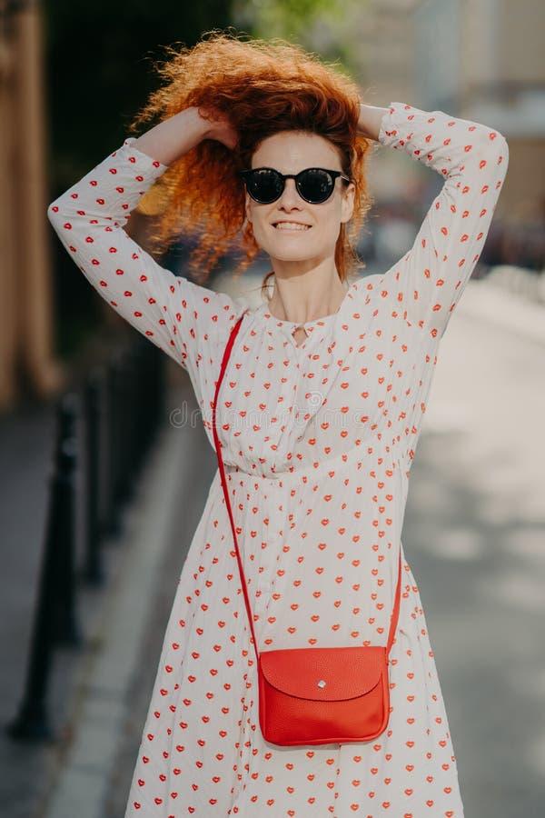 La bella donna allegra con capelli rossi croccanti, tiene le mani sulla testa, indossa gli occhiali da sole ed il vestito bianco, immagini stock