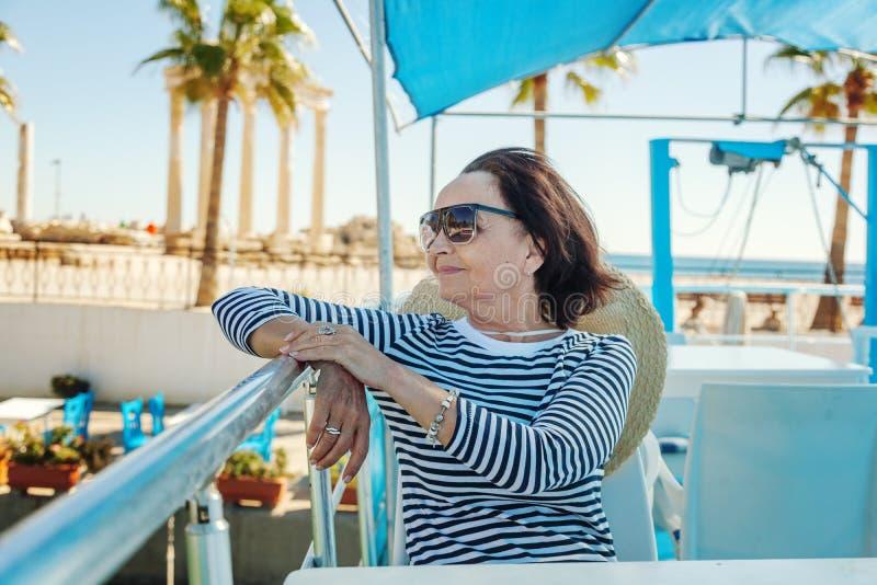La bella donna anziana alla moda viaggia su un yacht, su un backgro immagine stock libera da diritti