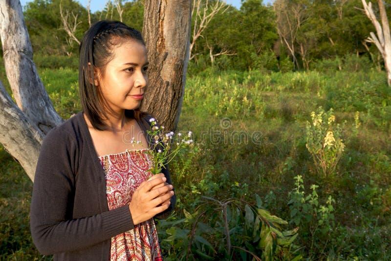 La bella donna asiatica è sorridente e tenente un gruppo di fiori selvaggi minuscoli in sua mano fotografia stock libera da diritti