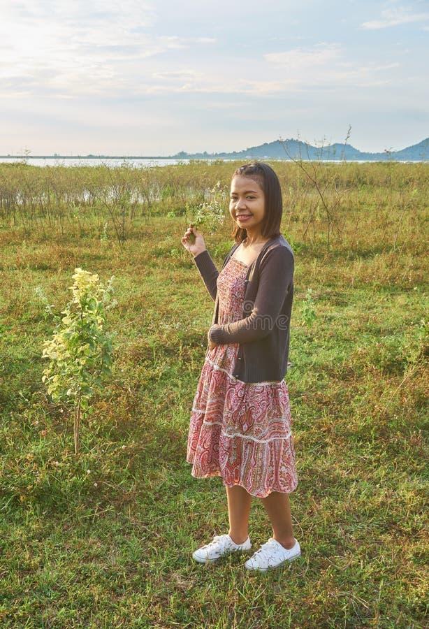 La bella donna asiatica è sorridente e tenente un gruppo di fiori selvaggi minuscoli in sua mano immagine stock