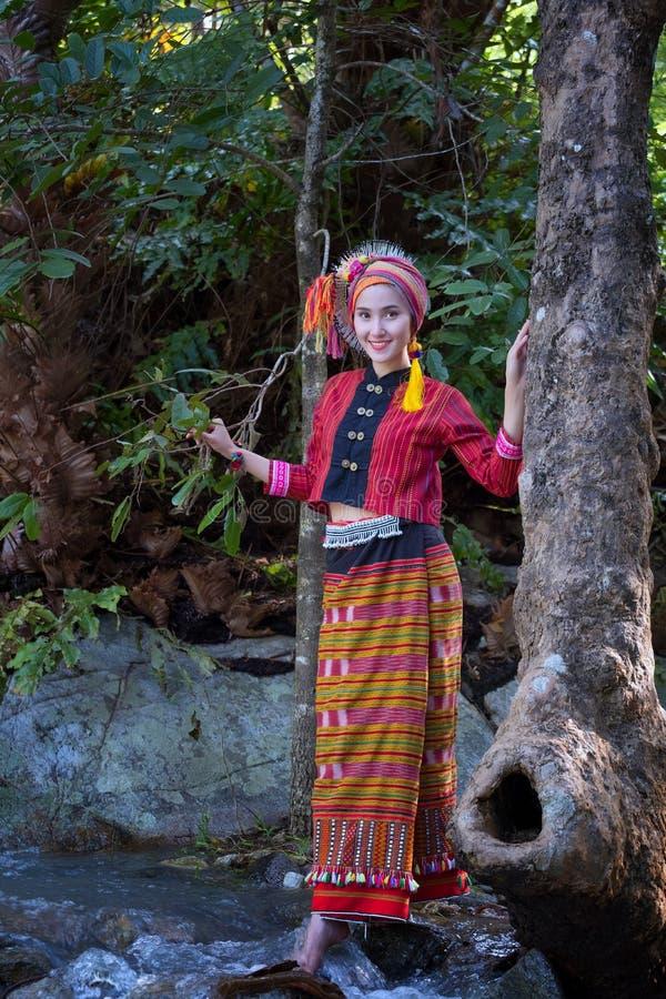 La bella donna asiatica con il vestito tradizionale tailandese esplora a wat immagini stock